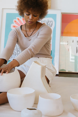 black female with ceramic pottery in workshop as art therapy