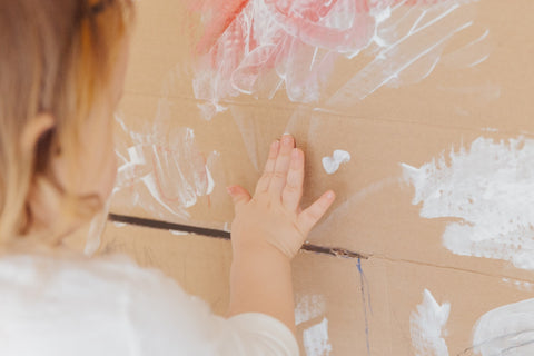 child painting with white paint at home on cardboard