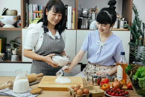 happy asian women learning how to cook