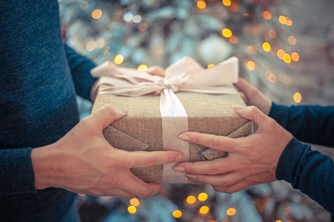 man giving wrapped gift to girl for christmas