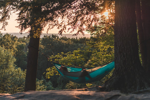 person relaxing and lying on hammock in the forest