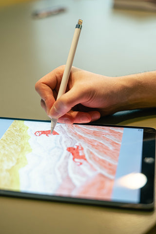 person sketching on drawing tablet