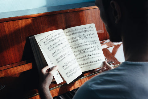 person studying music notes with piano