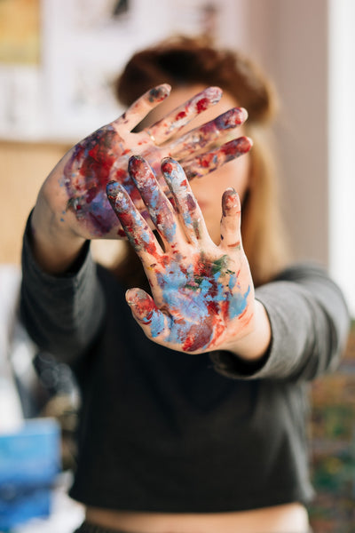 Person with red paint on hand