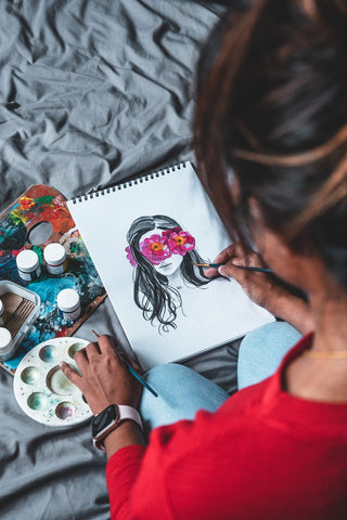 photo of person painting and drawing on paper