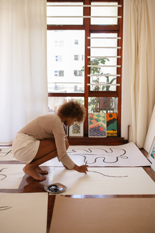 photo of woman painting simple art with white canvas on the floor