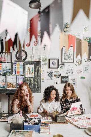 three women friends painting together