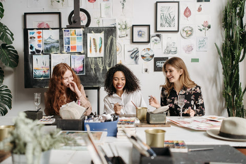three women happily painting and laughing in their desks