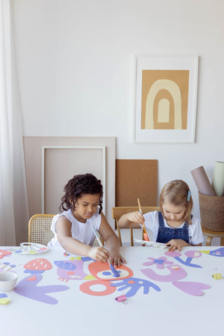 two little girls painting on table