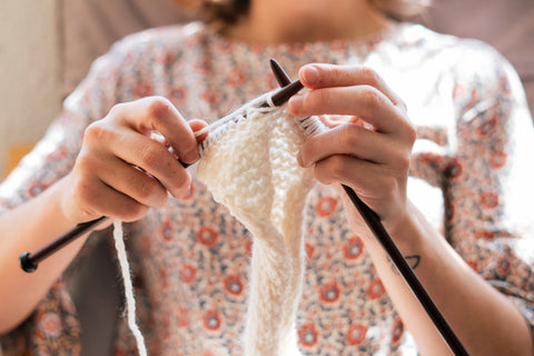 woman doing crochet with white yarn