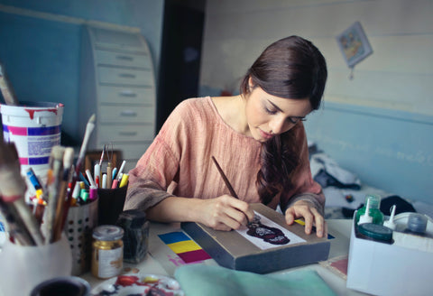 woman wearing pink painting with her paint by numbers kit