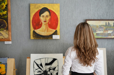 woman looking at painting on the wall