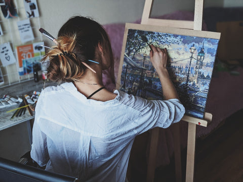 woman painting paint by numbers landscape