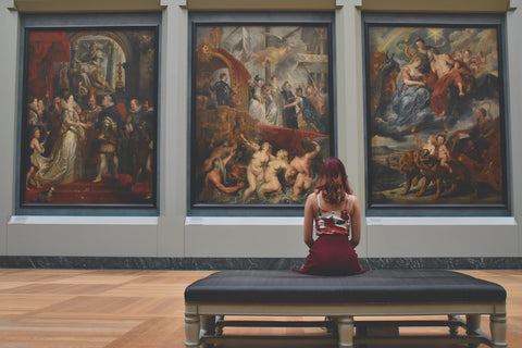 person sitting on bench looking at paintings