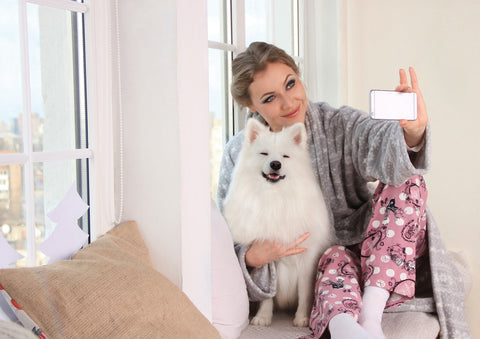woman taking a bright and clear photo of herself with white dog