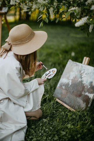woman painting outdoors in a white dress and hat