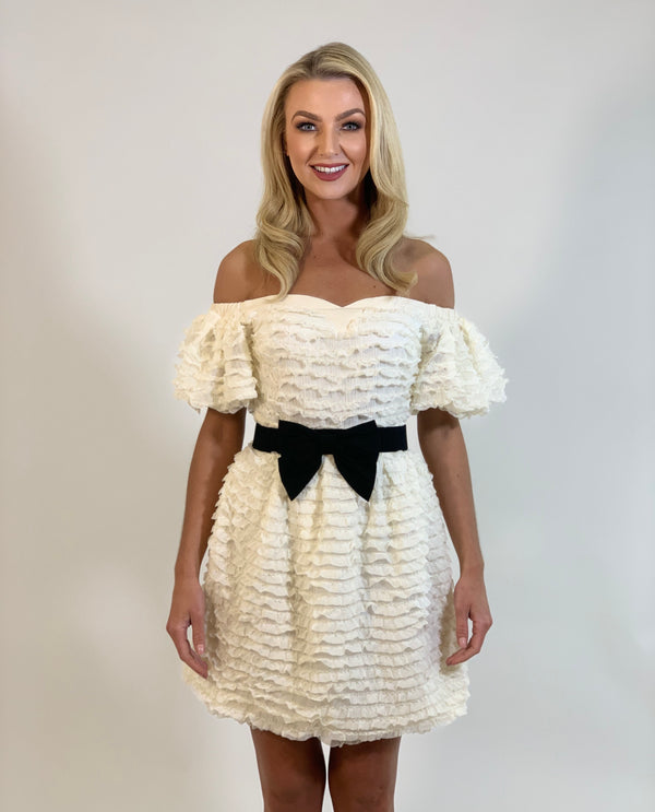 MSC model wears the Verona Dress in white, just above the knee with black bow belt- MSC the store