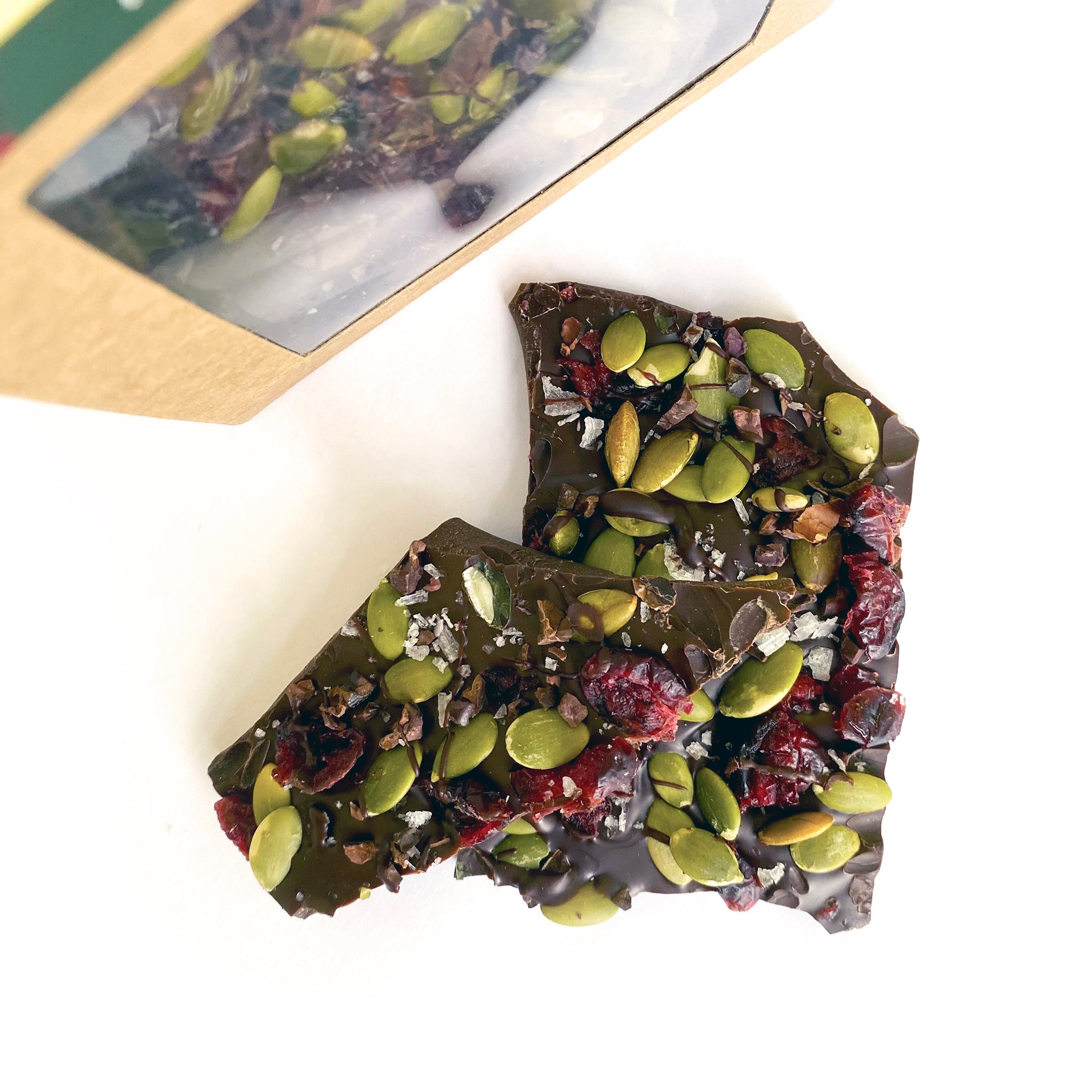 Pieces of chocolate bark out of packaging, exposing cranberries, toasted pumpkin seeds, cocoa nibs and flecks of sea salt