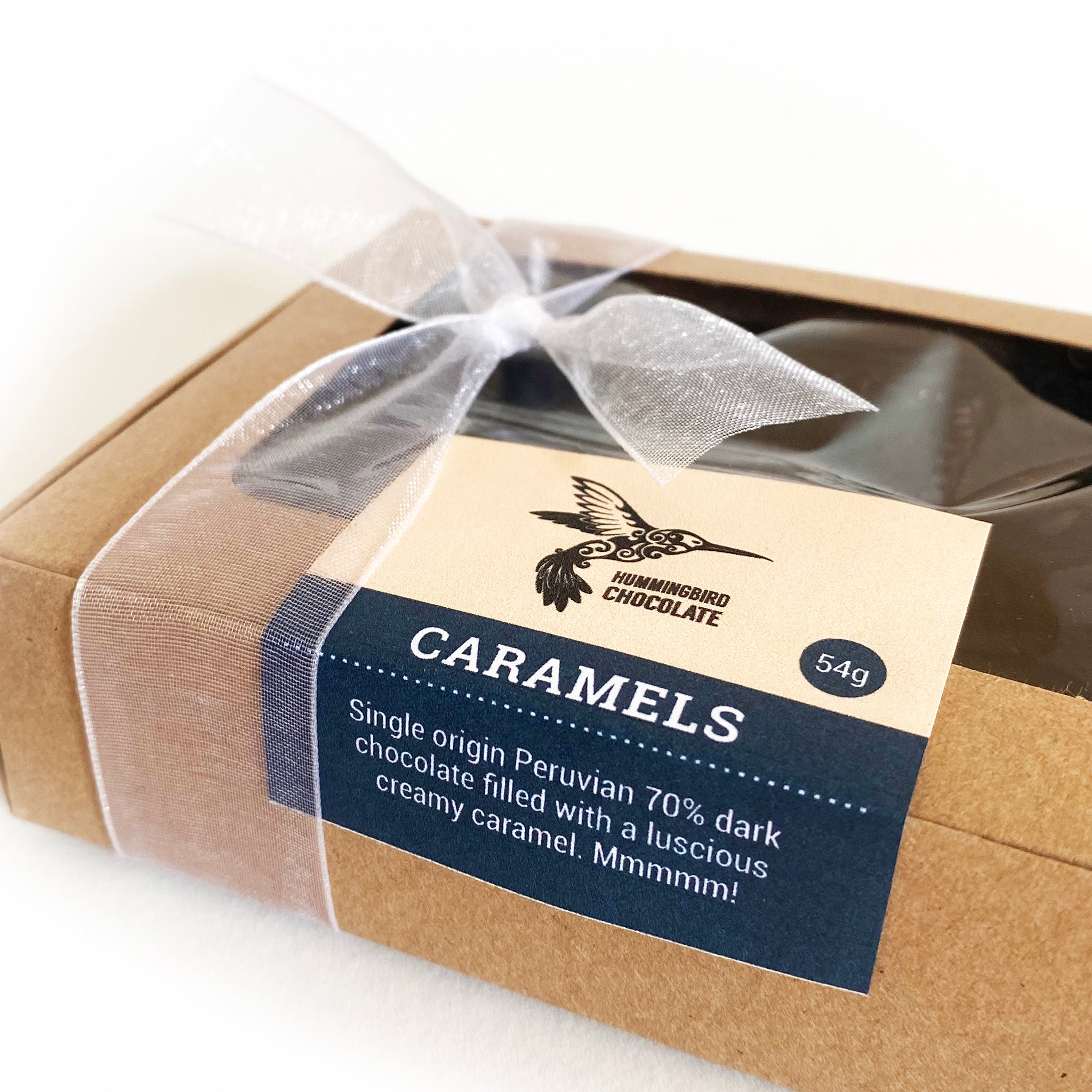 Side view of box of 6 dark chocolate filled caramels, wrapped in a paper box and bow