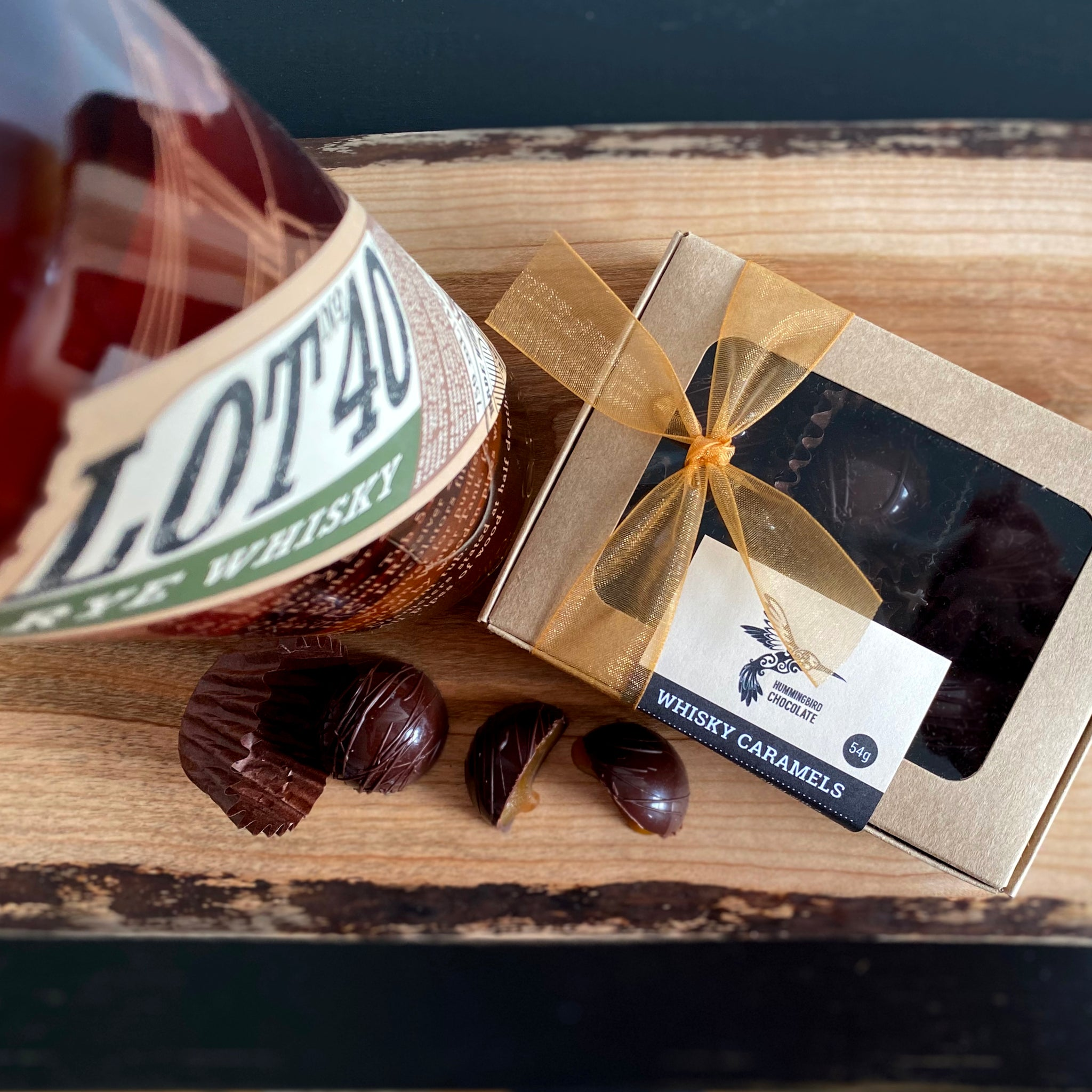 Box of dark chocolate whisky caramels, next to bottle of Lot No. 40 whisky,