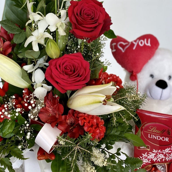 Elegant tall red and white Floral Arrangement including red roses, white lilies, orchids and seasonal flowers. Lindor Lindt Chocolate Bag and Teddy, not include but available in add ons.red rose Arrangement with oriental lily, stocks, or snap dragons, carnation and baby breath. elegant tall arrangement ideal for i love you , love, anniversary.