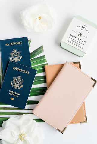 A pink Amelia rests on top of a Carmel one, with two passports fanned out to the left of the products