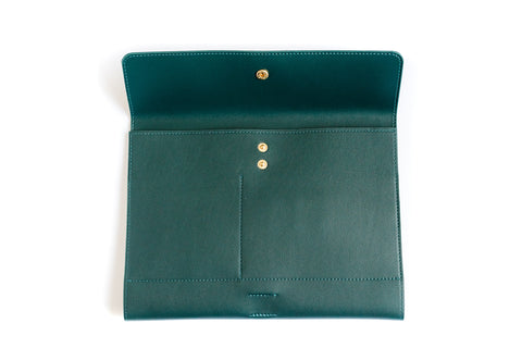 The forest green marilyn mini from a front perspective. The clutch is partially open showing the interior gold snap closure.