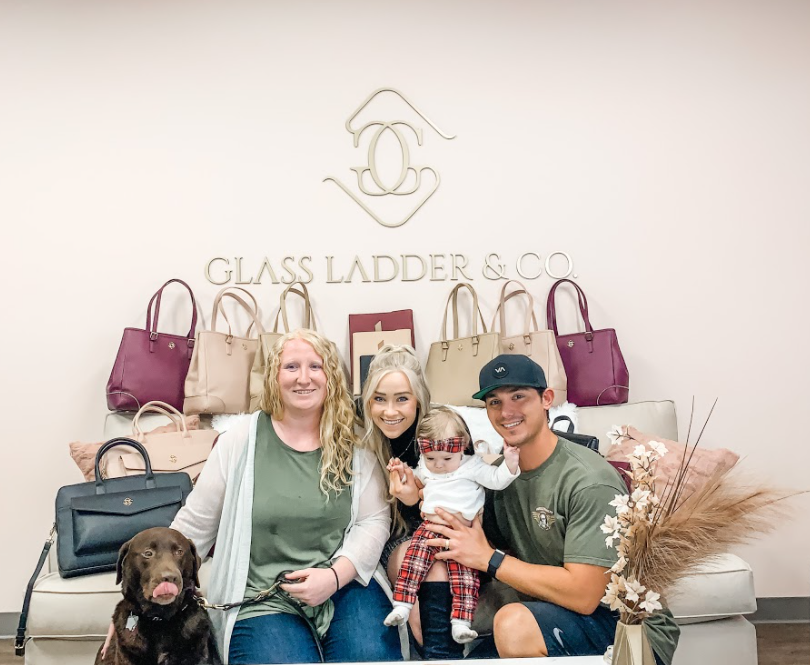 Pictured from Left to Right: Guide dog Lehmer, Danielle, Megan, baby Everly, and Daniel, posing with the Fall Collection Bags in front of a Gold Glass Ladder & Co wall decal sign.