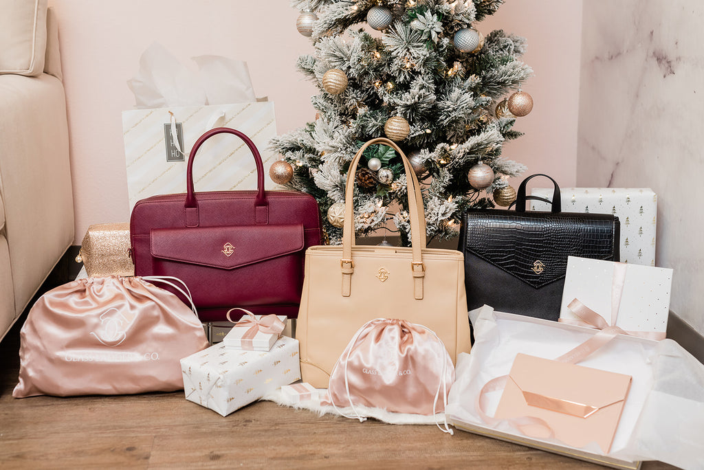 The Glass Ladder & Co. Fall Collection styled under a Christmas Tree with silky rose dust bags and white and gold gift boxes.