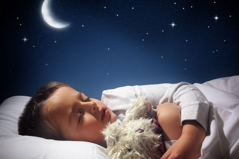 Child asleep in bed holding teddy bear