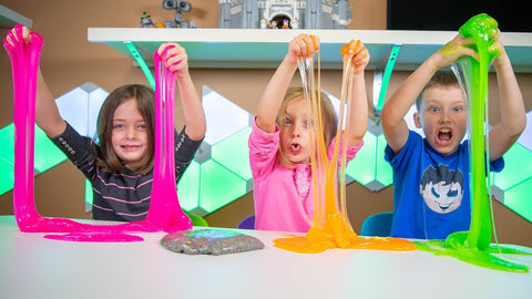Three children playing with neon coloured slime smiling