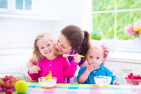 Mother with two children eating fruit and yoghurt and smiling