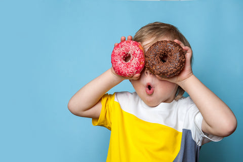 young boy holding two ring doughnuts to his eyes and pulling a funny face