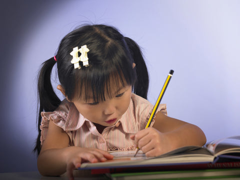 Young girl leaning on book using a pencil to write