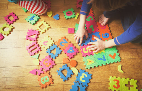 Floor blocks with alphabet and children playing with them