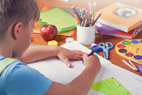 Child using coloured pencil to write and draw into book whilst leaning on desk