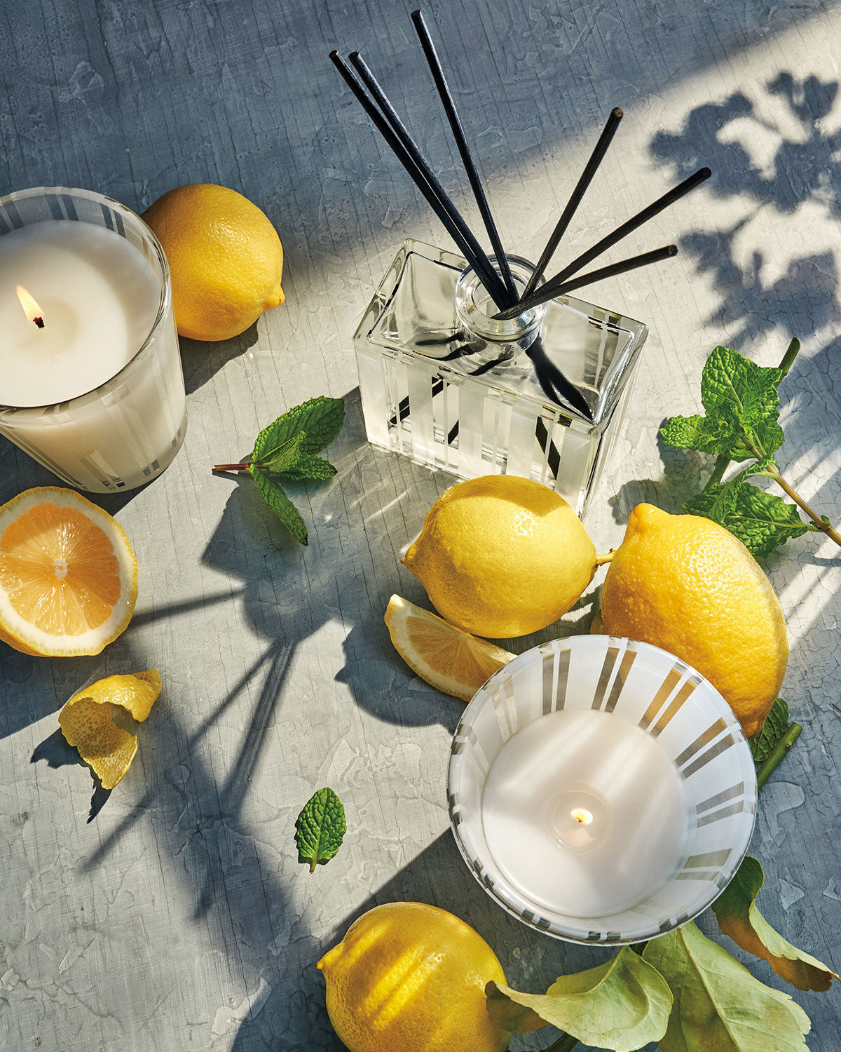 NEST Fragrances Amalfi Lemon & Mint Candles and Reed Diffuser Nestled Amongst Fresh Lemons