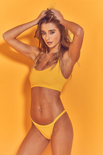 Model wears yellow abbey bikini top