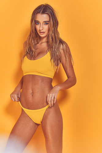 Model wears yellow Abbey bikini brief