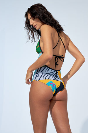 Women wearing a colourful tropical print one piece swimsuit. With open back, this bathing suit is made of recycled fibre fabric.