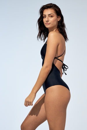 Women wearing black one piece swimsuit. With open back, this bathing suit is made of recycled fibre fabric.