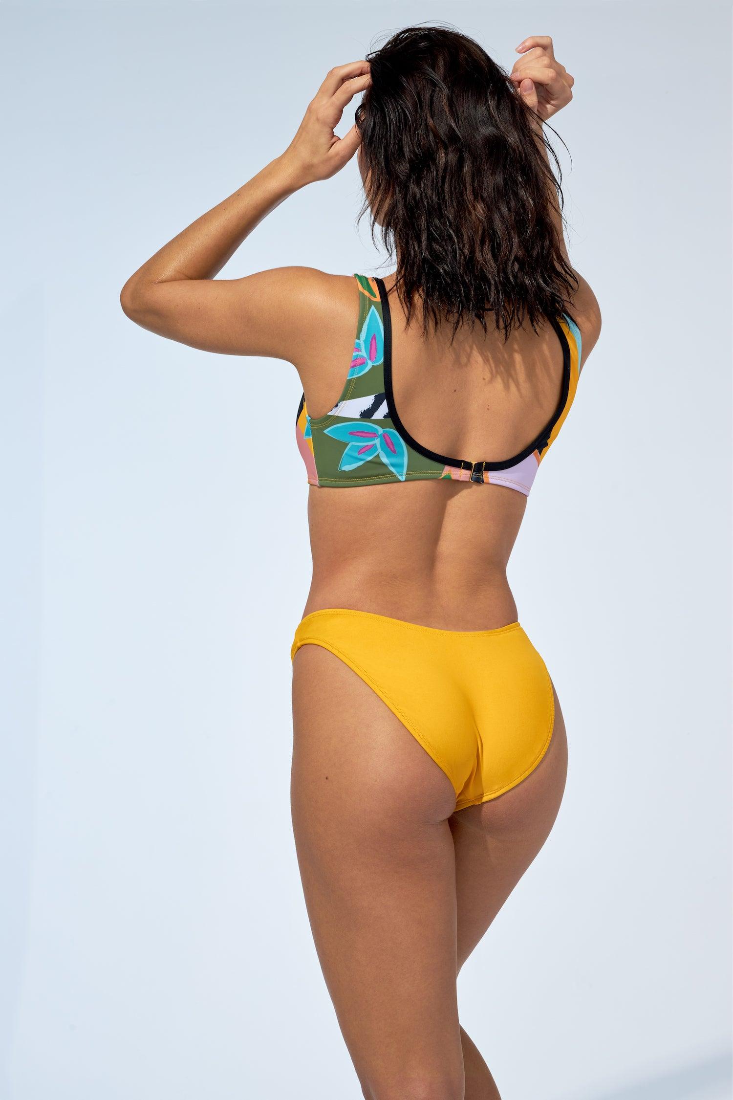Women tropical print sport bikini top and an indented low rise bikini bottom in yellow.