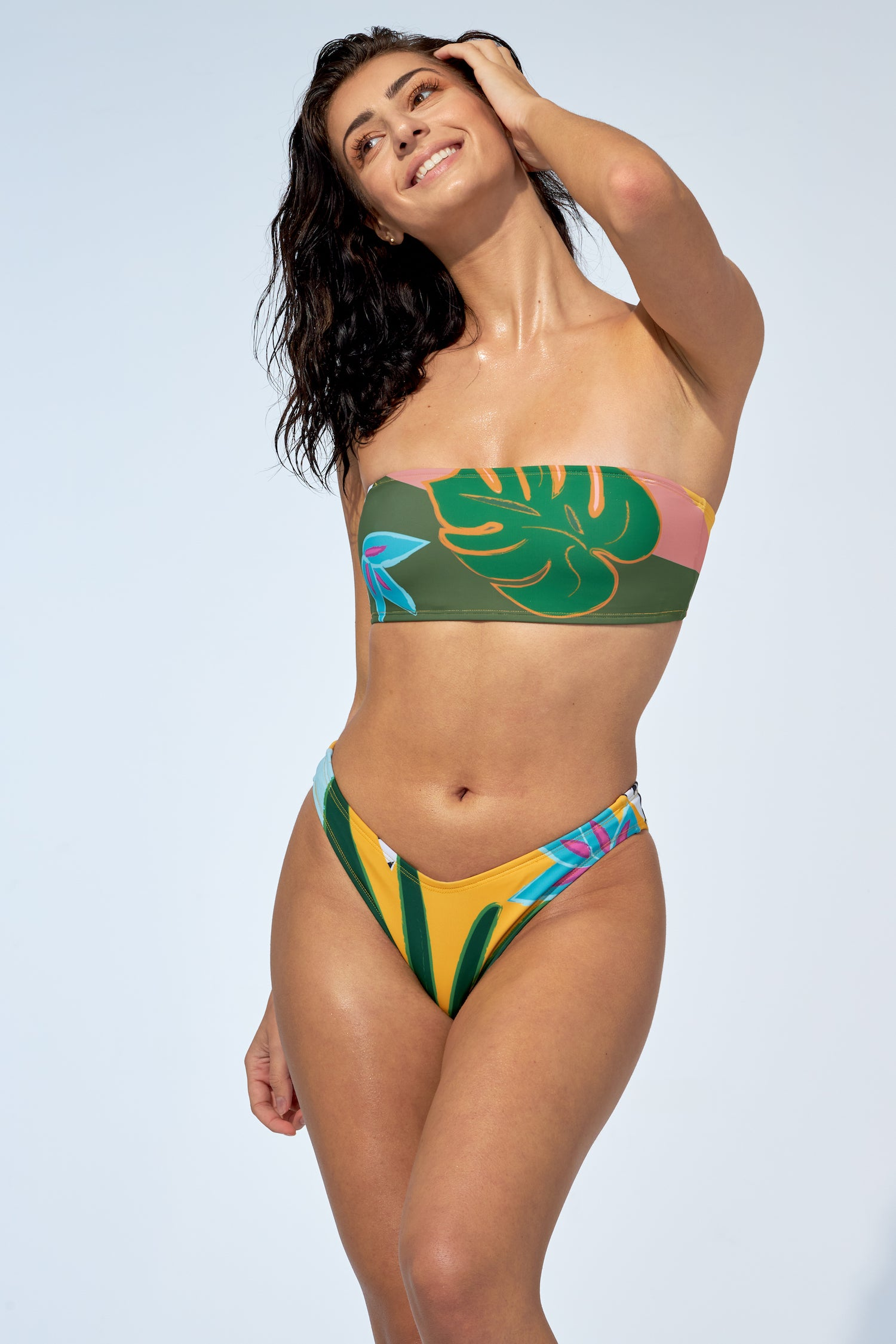 Women wearing tropical print bandeau bikini top and an indented low rise bikini bottom.