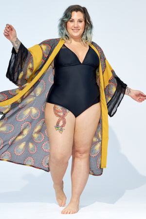 Women wearing black one piece swimsuit with paisley printed kimono cover up