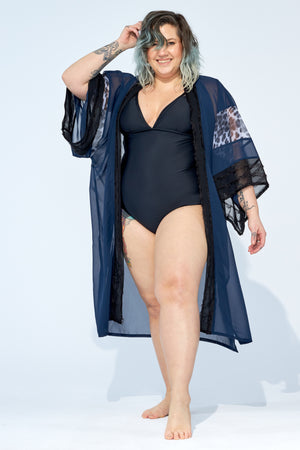 Women wearing beach kimono cover up on top of black one piece swimsuit.