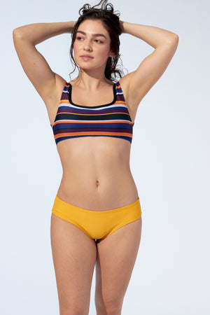 Women wearing striped bikini top and low rise yellow bikini bottom