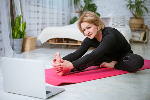 Older woman stretching at home