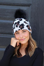 Load image into Gallery viewer, Leopard Pom Stocking knit hat 🖤 White leopard fleece lined cable knit hat with large pom accent.