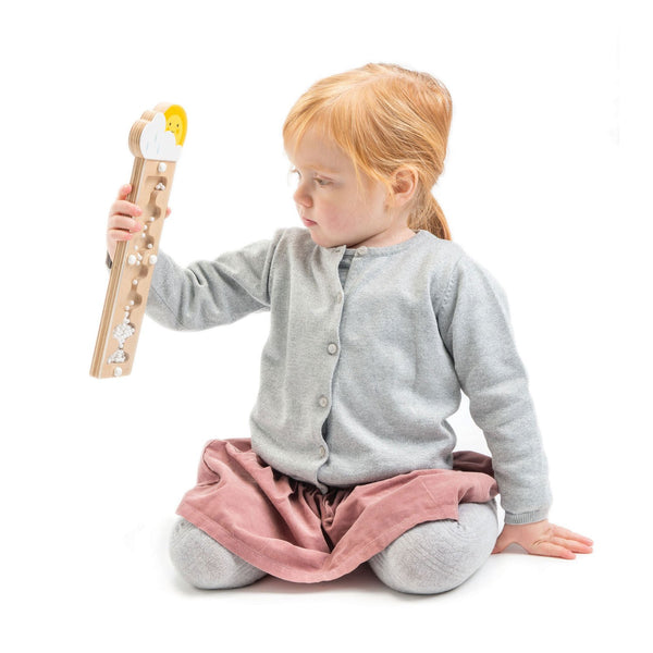 little girl playing with wooden rain maker toy