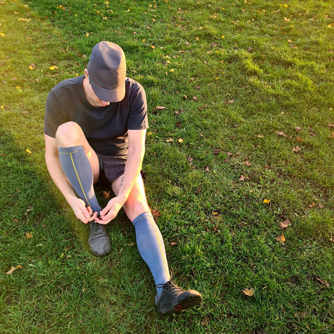 Man Wearing Hemp Compression Socks Tying Shoe Lace Sitting on the Grass, Hemp Sock Color Ensign Blue, Skin Friendly Eco Friendly Compression Wear, Antibacterial Durable Socks, Sustainable Active Wear | SHIN JARDBO